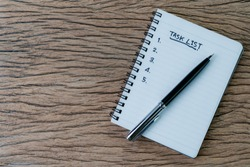 Task checklist in project management concept, pen on white paper notepad with handwritten headline as Task List and numbers listed on wood table, writing business project with tasks prioritize.