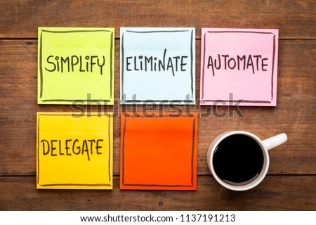 Task management concept: simplify, eliminate, automate, delegate. Handwriting on sticky notes against rustic wood board with a cup of coffee