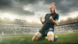 Taste or win. Young female soccer or football player in sportwear celebrating the goal in action at the stadium while gameplay. Concept of healthy lifestyle, professional sport, hobby, motion