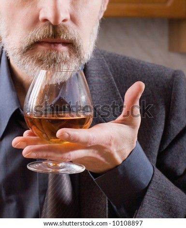 Taster. Man's hand holding a glass of classy brandy.