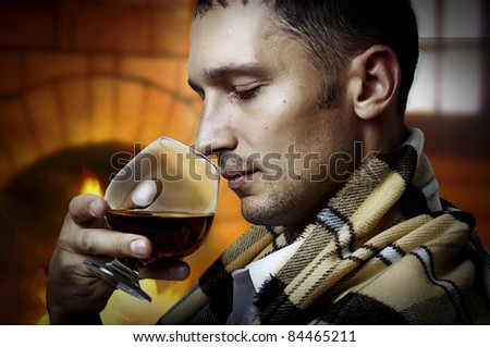 Taster. Young adult Man in tartan plaid holding in hand a glass of classy extra old brandy or cognac and smell it. He is inside home room siting about fireplace