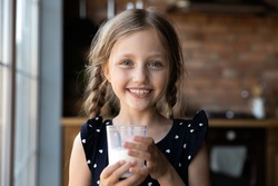 Tastes so good! Portrait of happy cheerful little girl holding glass of yoghurt looking at camera with milk mustache on face, cute child promotes healthy habit drink fresh farm dairy product every day