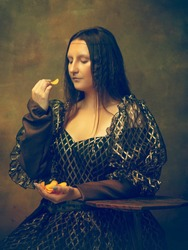 Tastiest chips. Young woman as Mona Lisa, La Gioconda isolated on dark green background. Retro style, comparison of eras concept. Beautiful female model like classic historical character, old