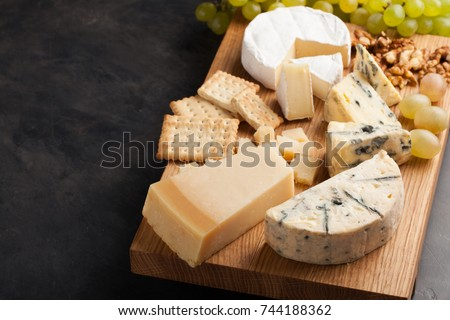 Tasting cheese dish on a wooden plate. Food for wine and romantic, cheese delicatessen on a dark stone table. with copy space.