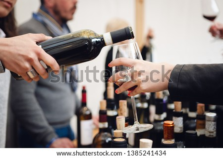Tasting experience with a female sommelier serving a glass of Barolo red wine in Alba (Piedmont, Italy) #1385241434