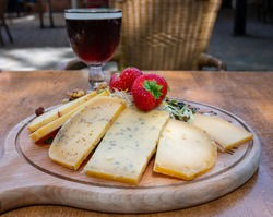 Tasting of different Belgian cheeses and dark strong Belgian beer served outdoor close up