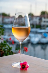 Tasting of local cold rose wine in summer on sunset with sail boats haven of Port grimaud on background, Provence, Var, France