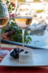 Tasting of local rose wine and soft french goat cheese in summer with sail boats haven of Port grimaud on background, Provence, Var, France
