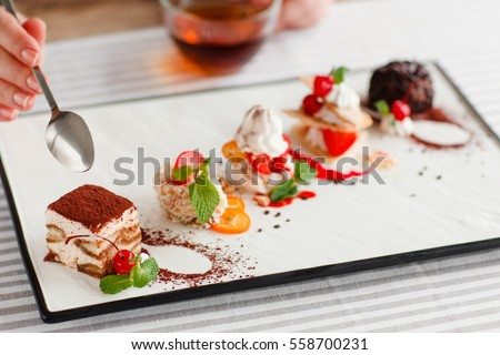 Tasting one cake from lots, close-up. Plate with five different sweet desserts, hand taking one. Degustation, choosing dessert for party or wedding, gastronomy, event organization concept #558700231