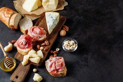Tasting prosciutto and cheese platter with parmesan, dorblu, almonds, nuts, bread and honey on a wooden board on a dark background. Appetizer, aperitif, snack table. Top view. Space for text