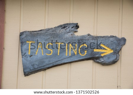 Tasting room sign with an arrow pointing to the wine tasting room at a large winery estate in the Russian River Valley of California. #1371502526
