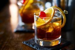 tasty alcoholic old fashioned cocktail with orange slice, cherry, and lemon peel garnish