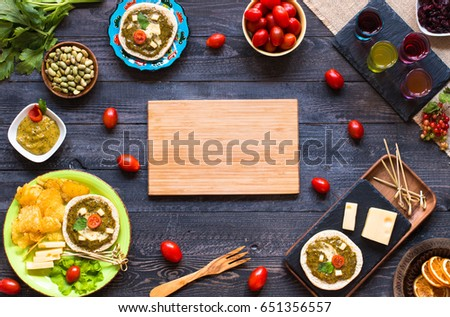 tasty and delicious bruschetta with avocado, tomatoes, cheese, herbs, chips and liquor, on a wooden background. Top view #651356557