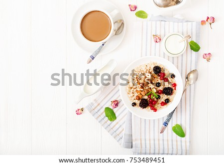 Tasty and healthy oatmeal porridge with berry, flax seeds and nuts. Healthy breakfast. Fitness food. Proper nutrition. Flat lay. Top view.