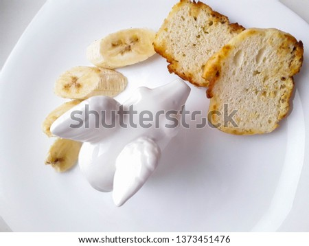 tasty and tasty lunch of bananas and kefir bread in a white plate on a white background #1373451476