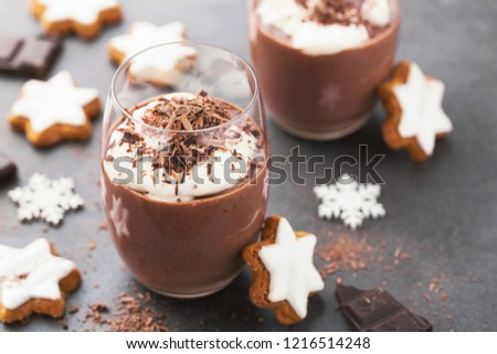 Tasty appetizing christmas cold chocolate dessert mousse served in glass with cream on top. Christmas cinnamon cookie as decoration. Closeup. Horizontal with copy space.