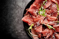 Tasty appetizing classic Italian bresaola with rocket salad and parmesan on black plate on black background. View form above. Top view. Horizontal