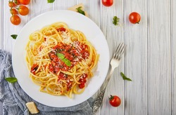Tasty appetizing classic Italian pasta spaghetti with tomato sauce, parmesan and basil on a plate on a white wooden table. Top view, horizontal. Flat lay. Copy space.