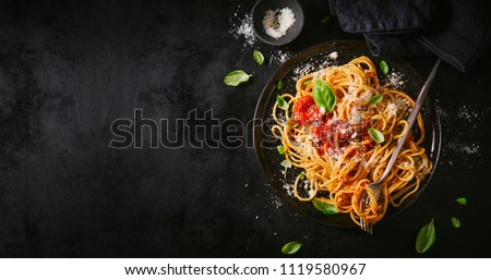 Tasty appetizing classic italian spaghetti pasta with tomato sauce, cheese parmesan and basil on plate on dark table. View from above, horizontal