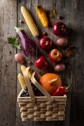 Tasty appetizing fresh autumn seasonal vegetables fruits in basket on wooden old background top view above copy space