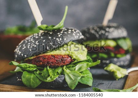 Tasty appetizing healthy vegan black burgers with beetroot, quinoa and avocado sauce served on wooden table. Horizontal with copy space. Concept of healthy food, clean eating #1184005540