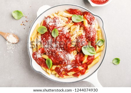 Tasty appetizing italian pasta penne with tomato sauce and cheese parmesan on white pan. Served on grey table. Horizontal with copy space.