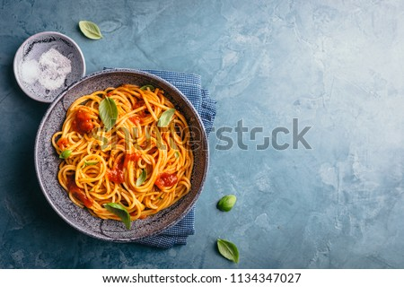 Tasty appetizing pasta served with tomato sauce, fresh tomatoes, basil and cheese in bowl on blue table. View from above