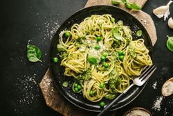 Tasty appetizing pasta spaghetti with fresh sauce pesto, green peas and cheese served on plate on black table. View from above. Ready to eat. Horizontal