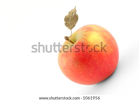 tasty apple with dry leaf on white