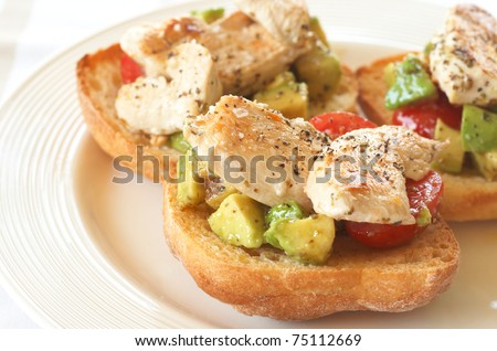 Tasty avocado, baby tomato and grilled chicken bruschetta on ciabatta