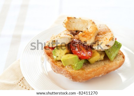 Tasty avocado, baby tomato and grilled chicken bruschetta on ciabatta bread