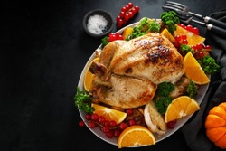 Tasty baked whole chicken with vegetables for Christmas or Thanksgiving Day served on table. View from above.