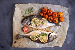 Tasty baked whole fish on baking paper. Baked sea bream with lemon, onion, herbs, cherry tomatoes, spices on dark rustic background. Grilled delicious fish. Diet and healthy food. Top view