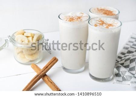 Tasty banana smothie or milkshake with cinnamon on white  background Foto stock ©