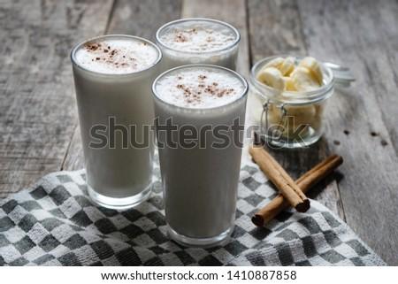 Tasty banana smothie or milkshake with cinnamon on wood background Foto stock ©
