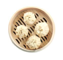 Tasty baozi dumplings in bamboo steamer on white background