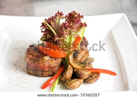Tasty beef steak grilled in a cast-iron ribbed fry pan with bacon decorated with vegetables and roasted mushrooms