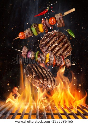 Tasty beef steaks and skewers flying above cast iron grate with fire flames. Freeze motion barbecue concept.