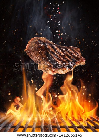 Tasty beef steaks flying above cast iron grate with fire flames. Freeze motion barbecue concept. #1412665145