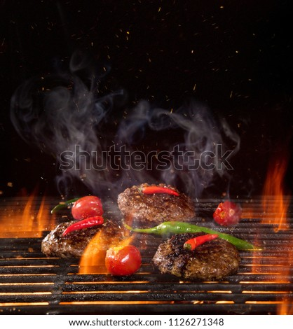 Tasty Beef steaks on iron cast grate with fire flames. #1126271348