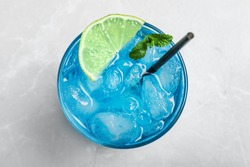 Tasty Blue Lagoon cocktail on light grey table, top view