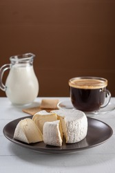 Tasty breackfast with creamy Camembert cheese on natural white wooden table with a cup of americano coffee and jug of milk