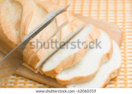 Tasty bread slices  cutting on a table - stock photo