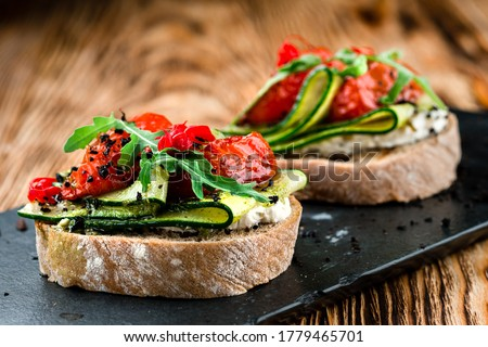 Tasty bruschetta with tomato. Easy cook, nutritious snack. Beautifully decorated catering banquet menu. Food snacks and appetizers for buffet. bruschetta with tomato and cucumber Stock fotó ©