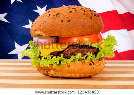 Tasty burger with American flag in background