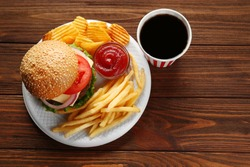 Tasty burger with snacks and coke on wooden table
