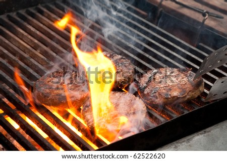 tasty burgers being cooked on a flaming barbecue