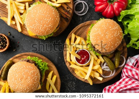 Tasty burgers, cheeseburgers, french fries, salad and red plaid kitchen textile, table top view. Three burgers or cheeseburgers, french fries and ketchup on dark background