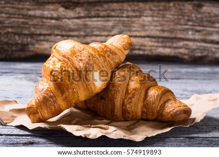 Tasty buttery croissants on old wooden table