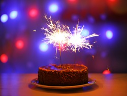 Tasty cake with sparklers on shiny background